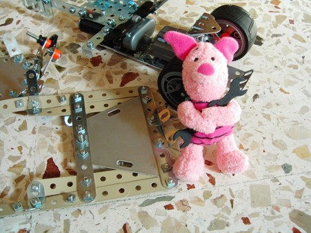 Piglet holds a spanner, surrounded by Meccano